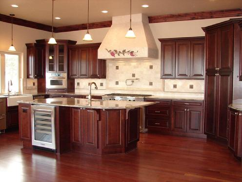 Dark stained kitchen cabinets. Cherry, with a formal design. Seating area  at one